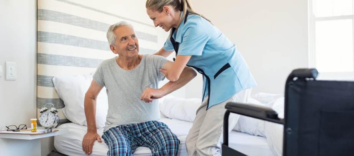 staff-helping-an-elderly-stand-up
